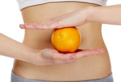 close-up of female hands holding an orange in front of belly - stock photo