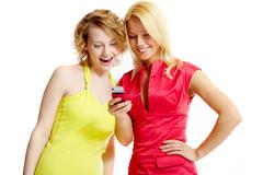 gorgeous girlfriends reading sms on mobile phone - stock photo