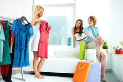 image of pretty females looking at their friend trying on smart dress while choo - stock photo
