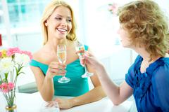 Gorgeous girls drinking alcohol on some occasion Stock Photos