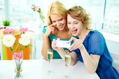 gorgeous girls looking at photo of themselves on telephone camera - stock photo