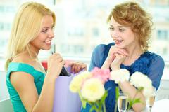 young girl showing birthday surprise to her friend - stock photo