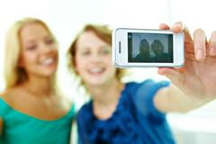 Happy girls taking photo of themselves on telephone camera Stock Photos