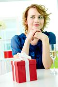 Gorgeous girl sitting at the table with flute and giftbox near by Stock Photos