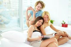 group of girls interacting while relaxing at home - stock photo