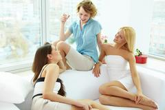 Group of pretty girls relaxing on sofa and chatting at home Stock Photos
