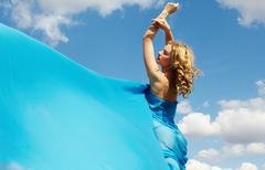 a beautiful girl wrapped in blue silk streaming in the wind - stock photo