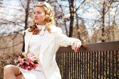 A pretty woman with flowers sitting on bench in park Stock Photos