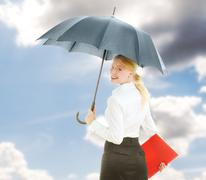 Happy businesswoman under open umbrella stretching her arm Stock Photos