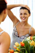 image of pretty female looking in mirror with smile - stock photo