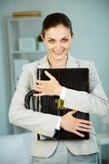 Portrait of smiling businesswoman with briefcase looking at camera in office Stock Photos