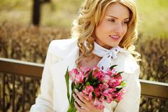 pretty blond with a bouquet looking away from camera - stock photo