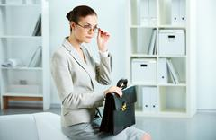 portrait of serious businesswoman with briefcase sitting in office - stock photo