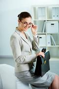 portrait of successful female with briefcase looking at camera in office - stock photo