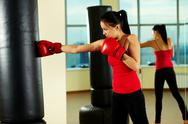 Stock Photo of portrait of young woman in red boxing gloves training in gym