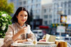 Image of young brunette in open air cafe looking at camera in urban environment Stock Photos
