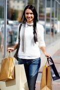 Image of happy female with paperbags walking down street Stock Photos