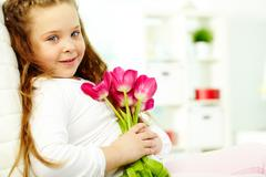 Portrait of happy girl with tulip bouquet looking at camera Stock Photos