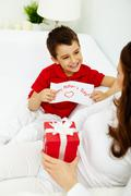 Cute lad with congratulating card looking at his mother with giftbox Stock Photos