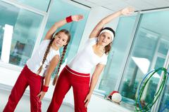 Portrait of healthy female and her daughter practicing physical exercise Stock Photos