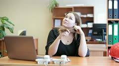 Lazy carefree woman sitting at the desk amd turning her hair on fingers Stock Footage
