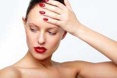 Posh woman with red lips and fingernails touching her forehead Stock Photos