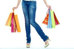 Image of shopaholic legs and shopping bags in hands Stock Photos