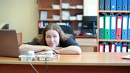 Bored young businesswoman sitting alongside a laptop and lazing Stock Footage