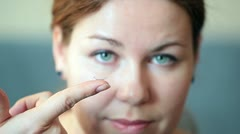 Young woman inserting clear contact lens in her eye - stock footage
