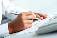 Close-up of business person hand with pen over document Stock Photos