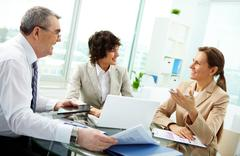 female leader talking to her workgroup about a new profitable idea - stock photo