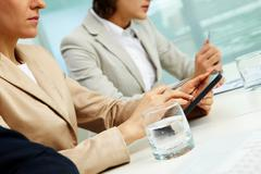 Businessman using her tablet pc, her colleagues sitting on both side of her, til Stock Photos