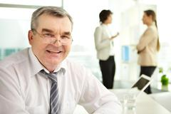 mature businessman looking at camera in working environment - stock photo