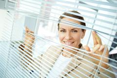 Confident business woman sliding apart blinds and looking at camera Stock Photos