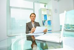 Concentrated business woman reading attentively the document before signing Stock Photos
