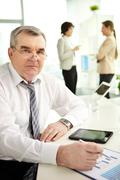 Mature businessman looking at camera in working environment Stock Photos