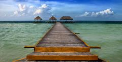 Yellow pier stretching into the ocean to daybeds Stock Photos