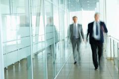 business people walking in the office corridor - stock photo