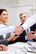 Businessmen shaking hands, their colleagues applauding cheerfully Stock Photos