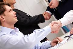 Group of business people shaking hands celebrating fruitful partnership Stock Photos
