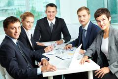 Stock Photo of successful business team with an experienced leader at the head looking at camer