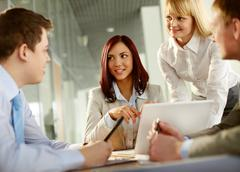 Business team of four taking part in a brief meeting Stock Photos