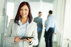 Business woman standing in foreground with a tablet in her hands, her co-workers Stock Photos