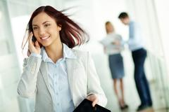 Pretty girl in formalwear talking on her mobile phone, her colleagues holding a Stock Photos