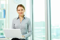 business lady with laptop looking at camera in office - stock photo