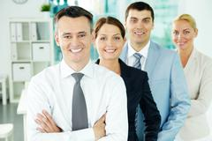 Portrait of business partners looking at camera with their leader in front Stock Photos