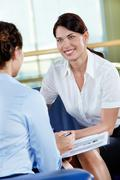 Portrait of confident businesswoman consulting her colleague in the office Stock Photos