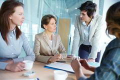 Image of four successful businesswomen interacting at meeting Stock Photos