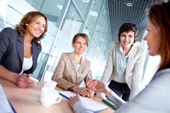 image of successful females listening to colleague at meeting - stock photo