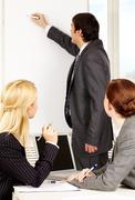 A business man drawing a plan on a whiteboard for his colleagues Stock Photos